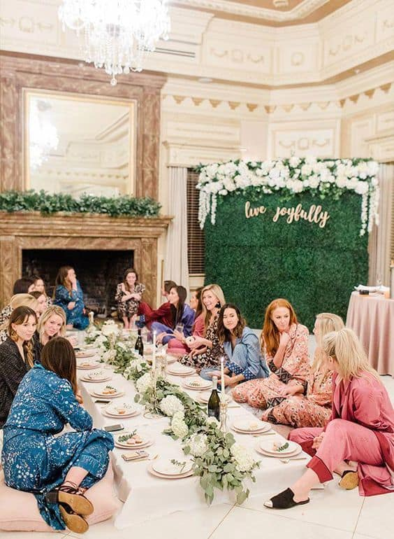 A bridal party of about 20 women sit around in silk PJs at a bridal shower