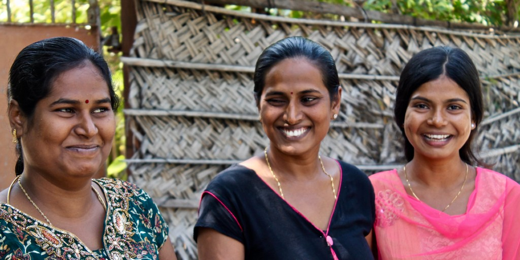 Three Sri Lankan Tamil women are stood side by side and smile widely at the camera. They all have thick black hair, brown skin, and are wearing gold jewellery.
