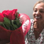 A smiling woman leaning towards a bouquet of red roses.