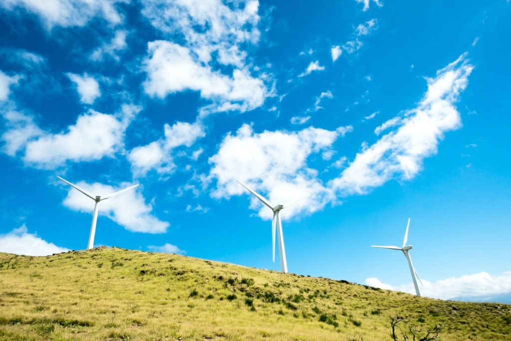 Three wind turbines are on a green hill. The sky above them is a bright blue with a lot of clouds.