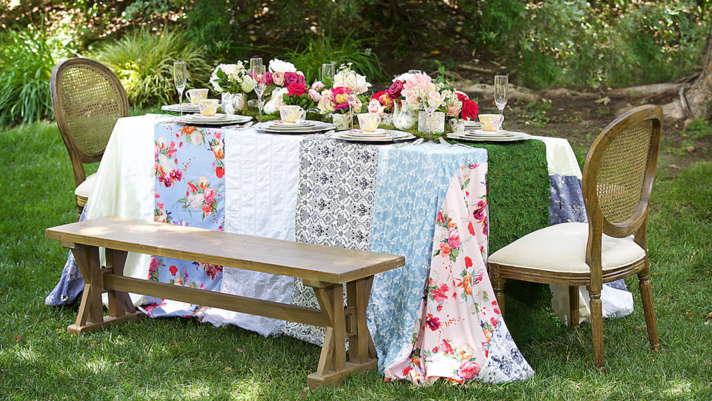 [Image description: A table is set up outside with patchwork table cover, floral arrangements and teacups.