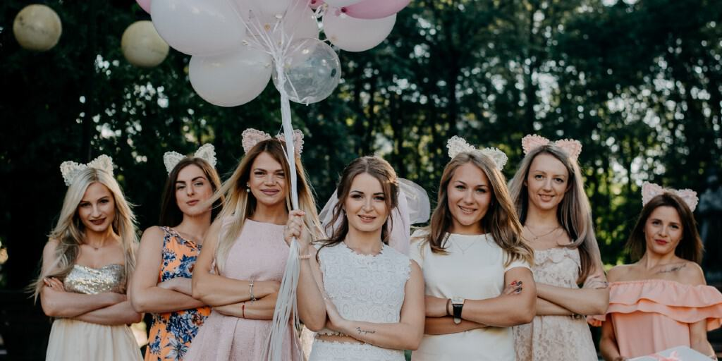 A bride stands with six bridesmaids who are al wearing kitty ear hairbands, holding balloons.