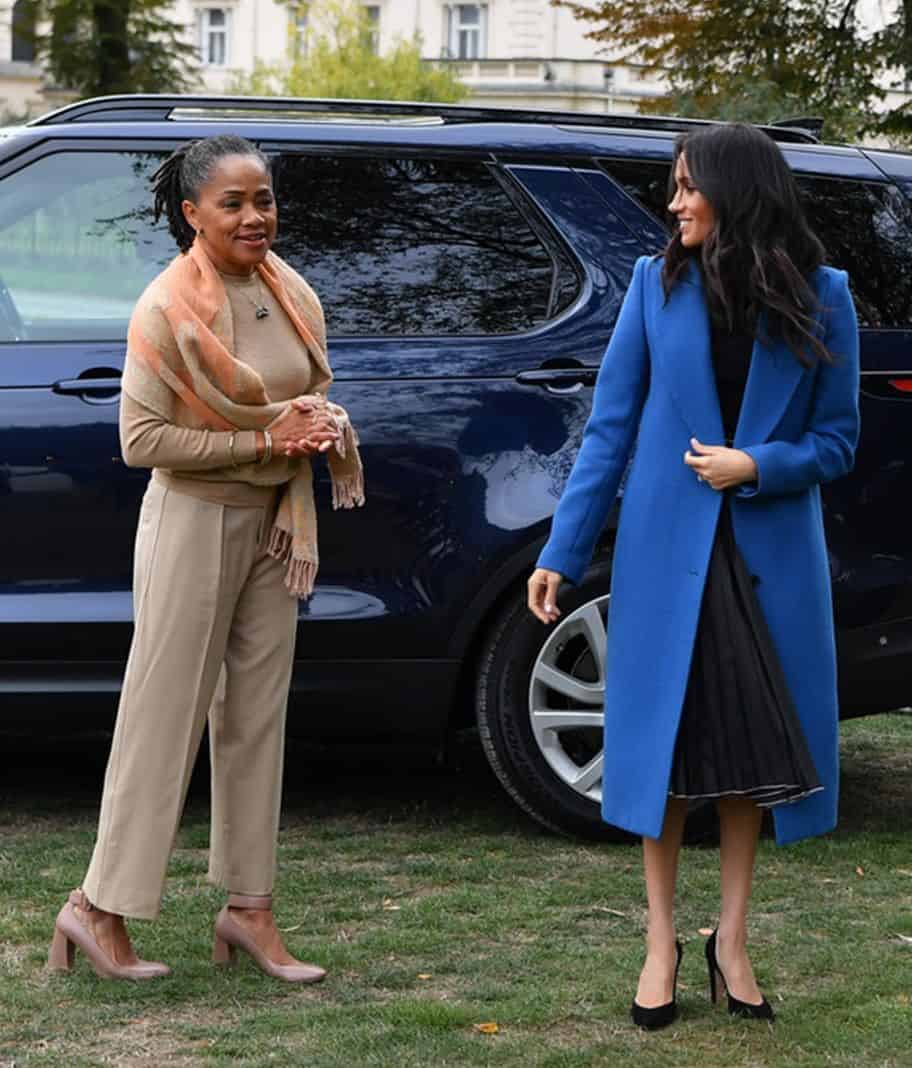 [Image Description: Meghan Markle is looking down smiling and walking on grass wearing a blue coat and black top and skirt. Her mother is walking to the right of her and wearing light pink clothes] via Ben Stansall/Getty Images