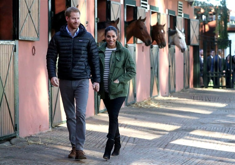 [Image Description: Meghan Markle, a brown-haired woman with her dark hair pulled back is wearing a striped sweater, green jacket, black boots and jeans with a hand in her pocket and the other hand holding Prince Harrys, a red-haired man in a black jacket and grey trousers] via Samir Hussein/Getty Images