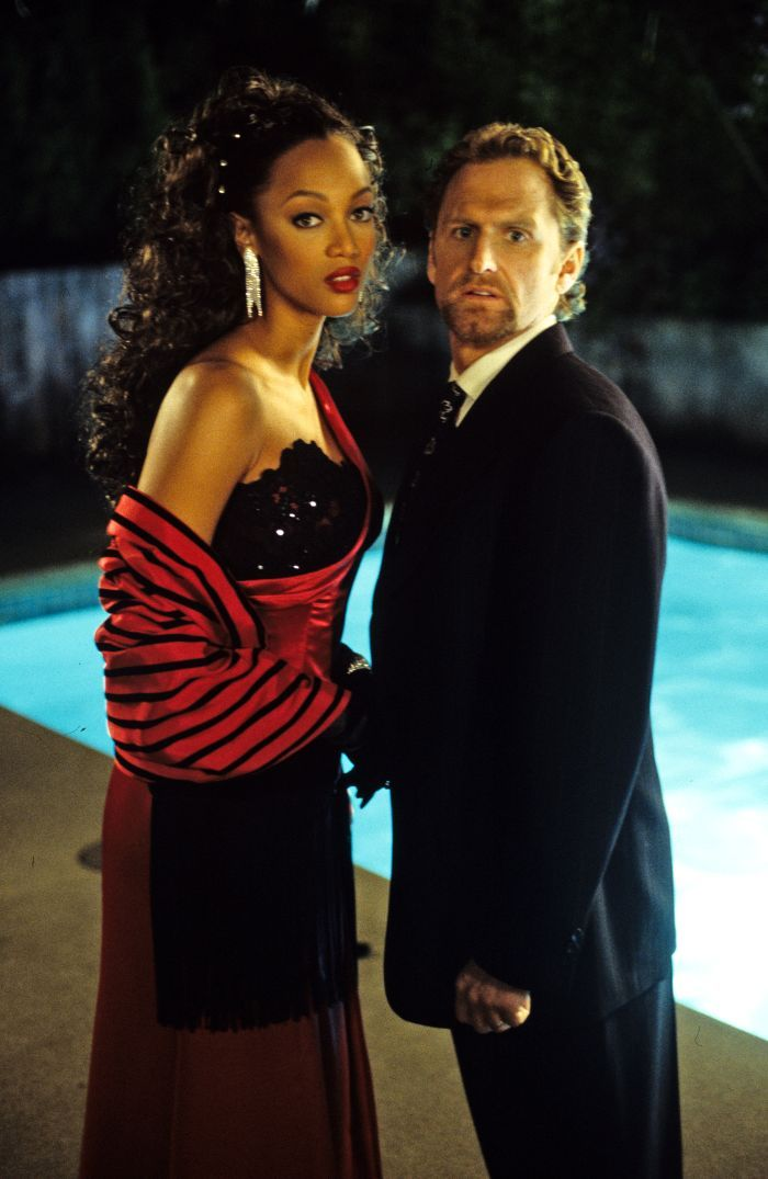 A tall, black woman and white man stand facing each other and looking towards the camera. The woman's hair is pulled back and in voluminous curls, and she wears a red satin dress with a black lace bodice and matching shawl. She is also wearing a pair of dangling diamond earrings.