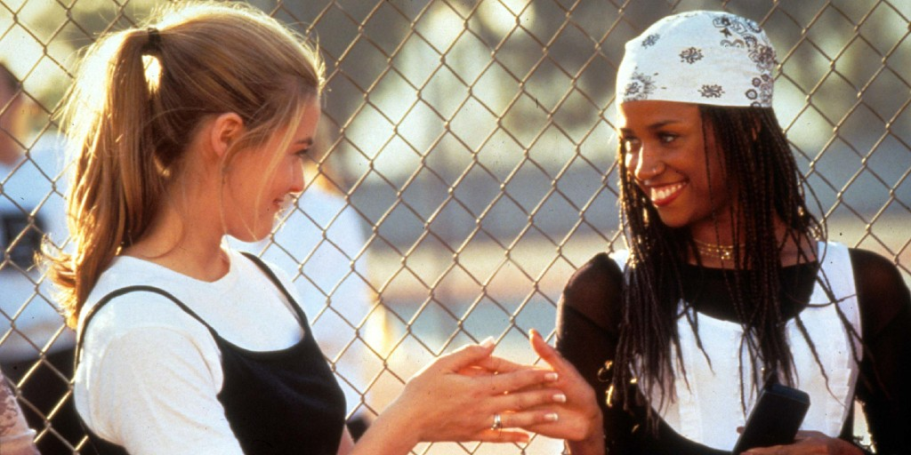 Two young women - one who is white and blonde and one who is black with long braids under a bandana - high five each other while leaning against a tennis court fence. They are both wearing monochrome outfits.
