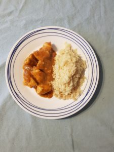Butter chicken and rice pilaf sit on a white plate.