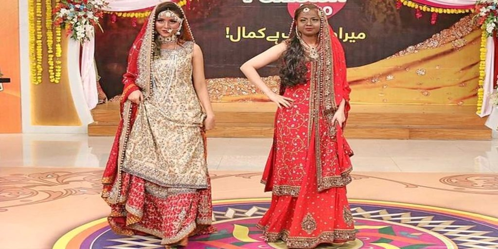 image description: two fair skinned Pakistani girls are wearing bridal dresses with their faces made up in shades much darker than their skin tone