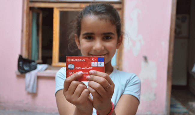 A little girl holding an e-card with both her hands showing it to the camera and smiling