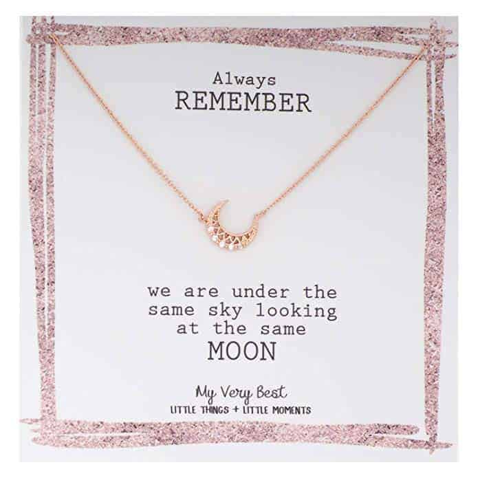 """A small gold crescent moon necklace with small pearls. The packaging reads """"Always remember we are under the same sky looking at the same moon."""""""