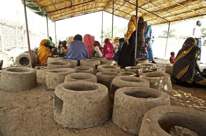 Several stoves made of clay on the ground outside under a shade with people gathered at a distance.