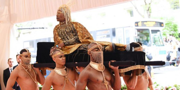 Billy Porter, a black man reclines on a litter, dressed in golden robes, wearing a golden wig and bold gold makeup. The litter is carried by topless black men wearing elaborate gold jewelry.