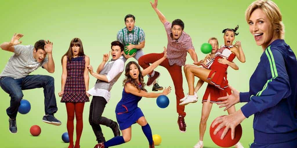 Against a green backdrop, several students (the cast of Glee) are dodging dodgeballs thrown by a blue-and-green tracksuit wearing coach smiling at the camera.