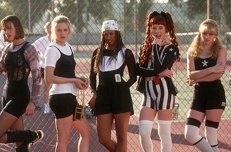 Five young women lean against a tennis court fence wearing a variety of monochrome sports outfits.