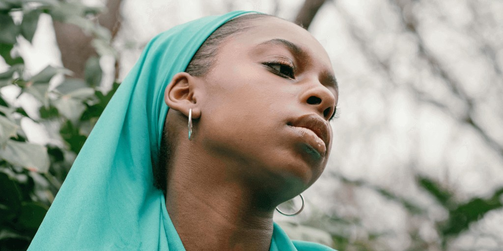A black woman in a teal hijab is looking down sadly.