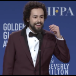 Photo of Ramy smiling into a mic. The Golden Globe award backdrop is behind him