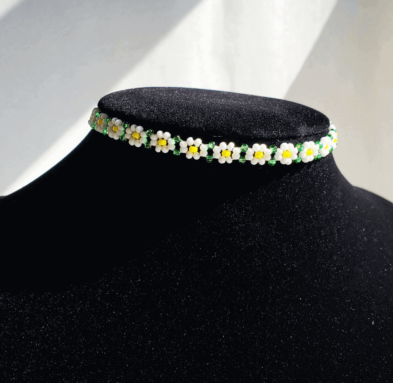 A beaded choker featuring a pattern resembling daisies on a black mannequin.