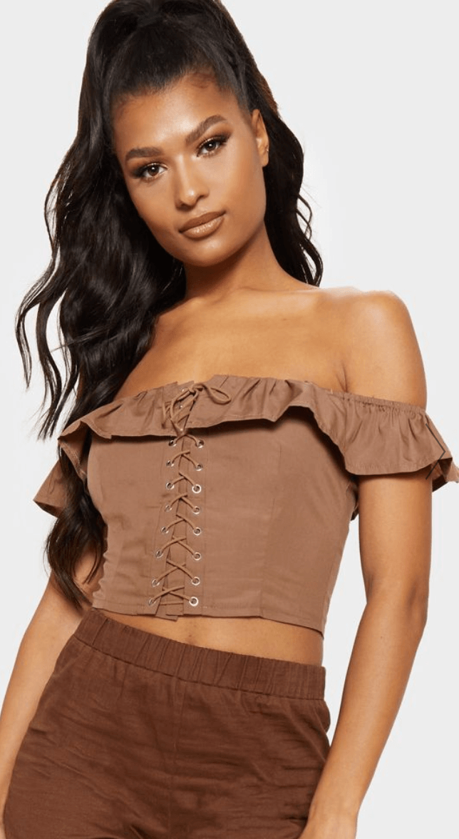 A woman wears a brown off-shoulder corset top with a lace-up front.