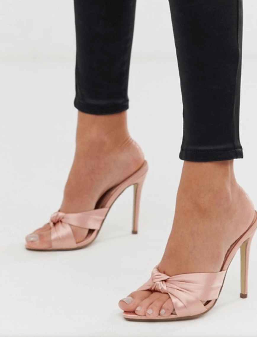 A woman wears a pair of satin pink mules.