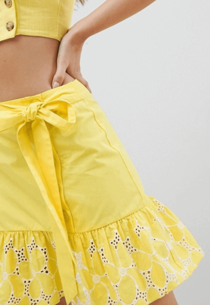 A bright yellow mini skirt with a broderie anglaise hem and tie waist.