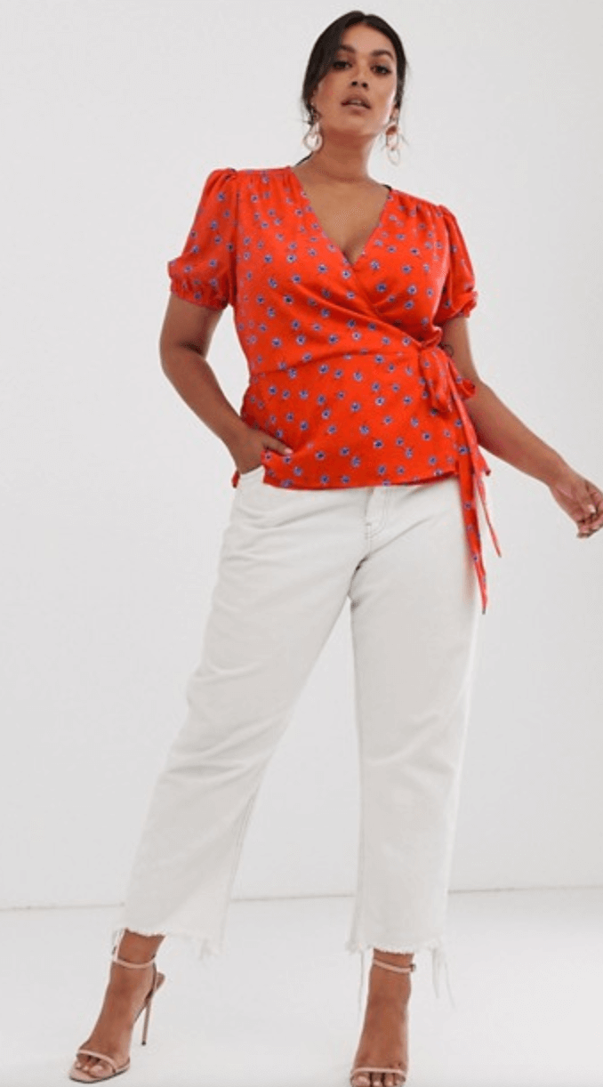 A woman wears a red satin wraparound top with balloon sleeves and a blue floral pattern.