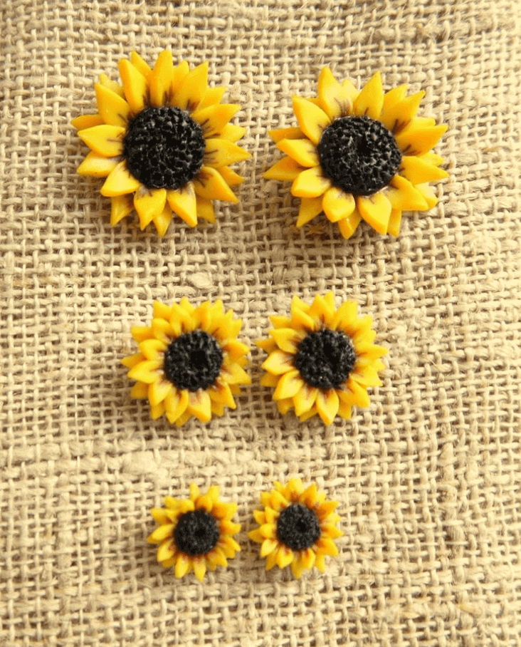 Three pairs of stud earrings resembling sunflowers in different sizes against a textured brown fabric.