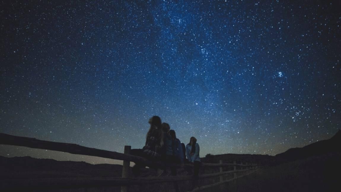 [Image description: Four women are sitting on a wooden face in a field gazing up at the starry universe.] Via Free-Photos on Pixabay