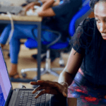 [Image description: A black man and woman are at a desk, in front of two computers with code on the screens. The woman is leaning in as she explains something to the man. In the background, another woman is seated at a computer.] Via NESA by Makers on Unsplash