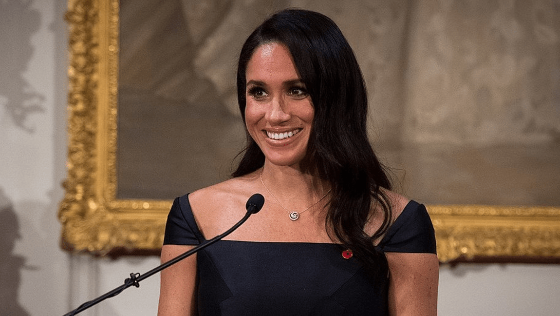 [Image Description: Meghan Markle stands in front of a microphone smiling, and wearing a black dress] via Office of the Governor-General of New Zealand