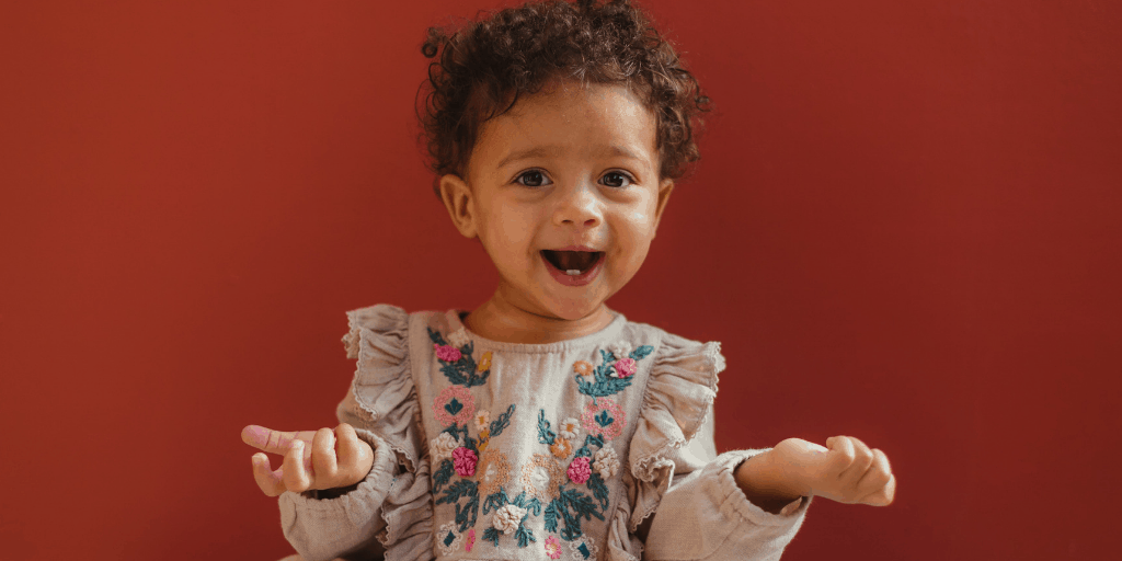 [Image description: Baby with curly hair laughs while holding their hands up.] Photo by Humphrey Muleba on Unsplash