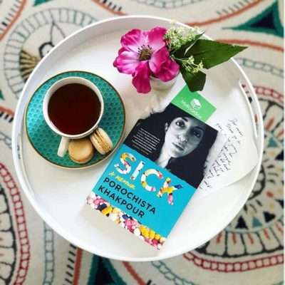 On a round, white tray is a pink flower, a cup of coffee, macaroons, and a copy of Sick: A Memoir.