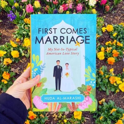 A hand is holding a copy of First Comes Marriage in front of a flowery background.