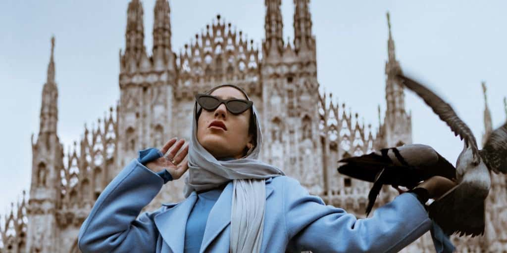 A Muslim woman is standing in front of a Cathedral wearing a grey hijab, blue coat and top, and black sunglasses. There are two pigeons on her left arm as she is looking up.