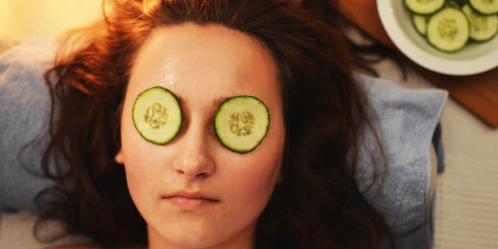 A woman with cucumbers over her eyes relaxing.