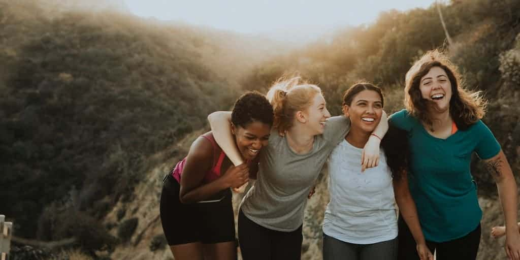 Outside in nature, on a hiking trail, four women are laughing and chatting. Their arms are slung across each others' shoulders.