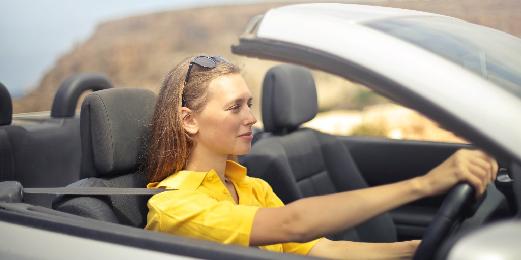 A woman with sunglasses in her hair wearing a yellow T-Shirt is driving a white covertable car.