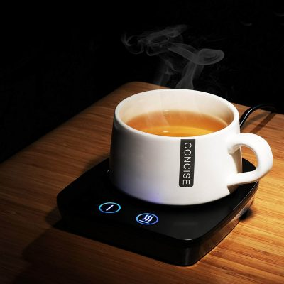 A cup of steaming tea rests on a coaster-like warming device.
