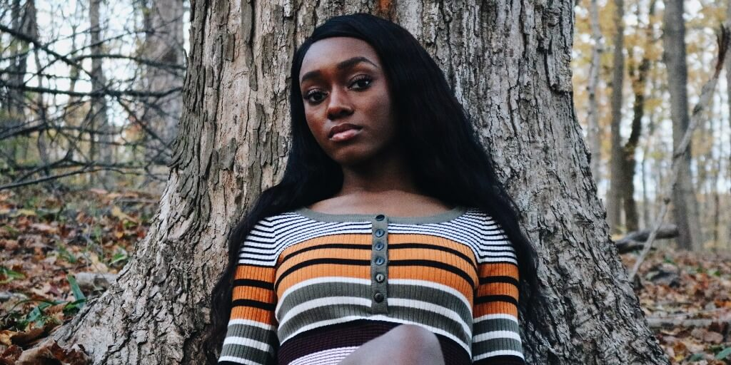 woman wearing a stripy jersey looks into the camera and leans against a tree trunk.