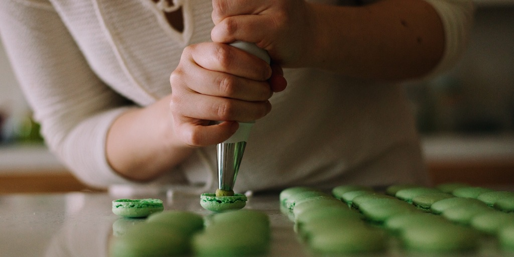 A body leaning over a tray of green macarons while icing one.