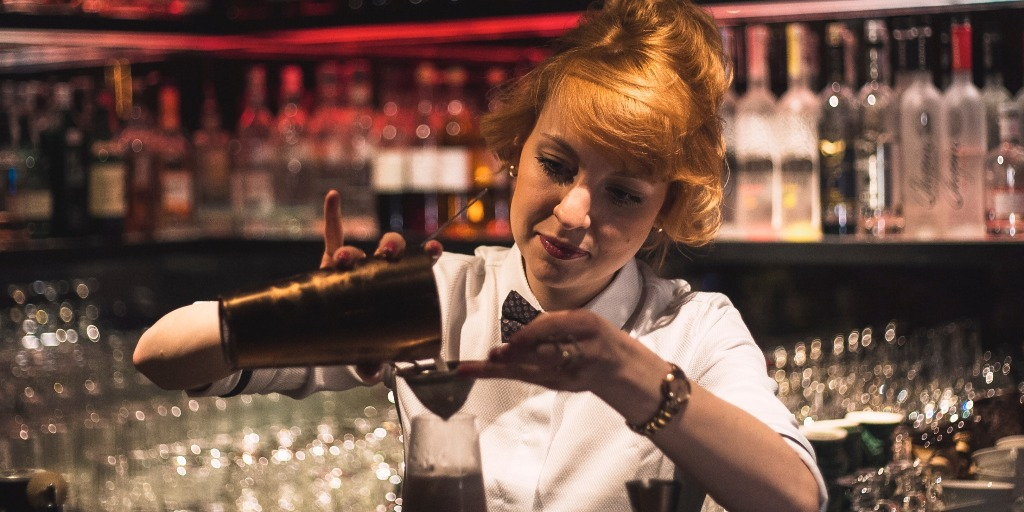 A woman pouring a cocktail at a bar.