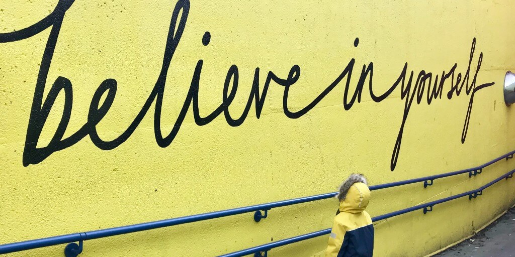 "A child wearing a coat and hood stares up at a wall, written in cursive letters are the words, ""believe in yourself."""