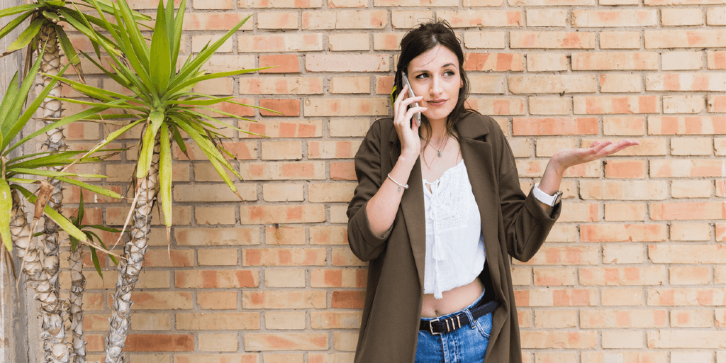 A dark-haired woman stands against a red brick wall. She is on the phone, expressing disinterest as she holds a hand out in ways of a shrug.