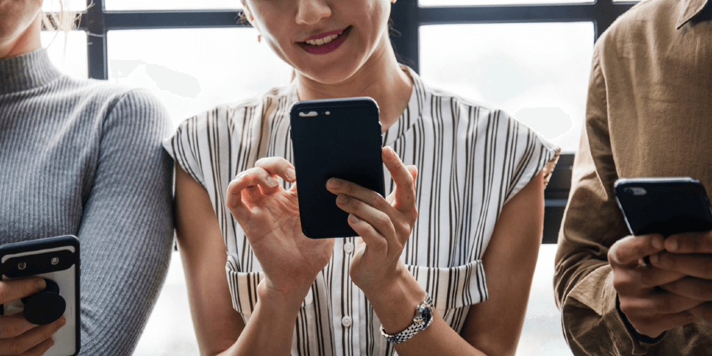 A woman in a white top with black stripes is smiling as she uses her phone.