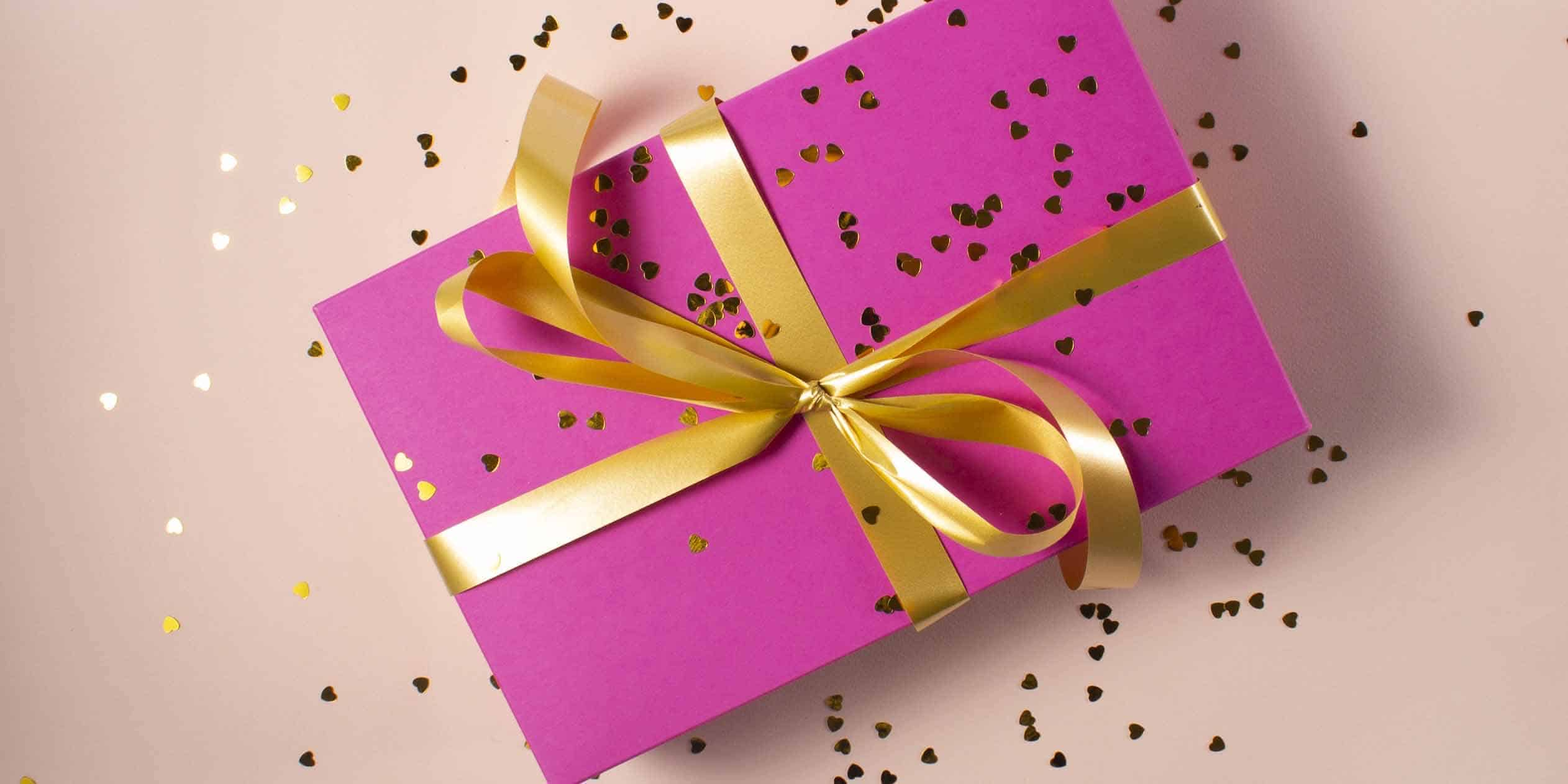 A pink box wrapped in a gold ribbon, covered in gold confetti.