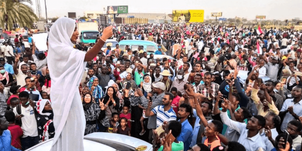 A woman draped in white garments stand on a car addressing a large crowd in Sudan.