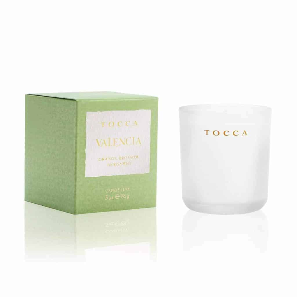 A light green box with gold text and a white candle.