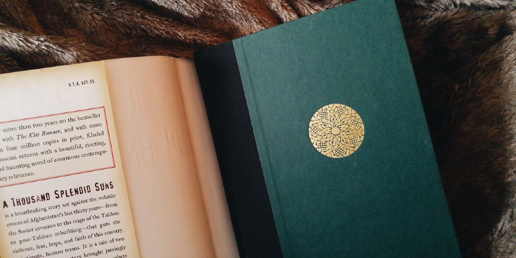 A hardback of A Thousand Splendid Suns lies face-up on a blanket. The cover is emerald green with an interpretive etching of a gold sun. The book jacket rests next to it.
