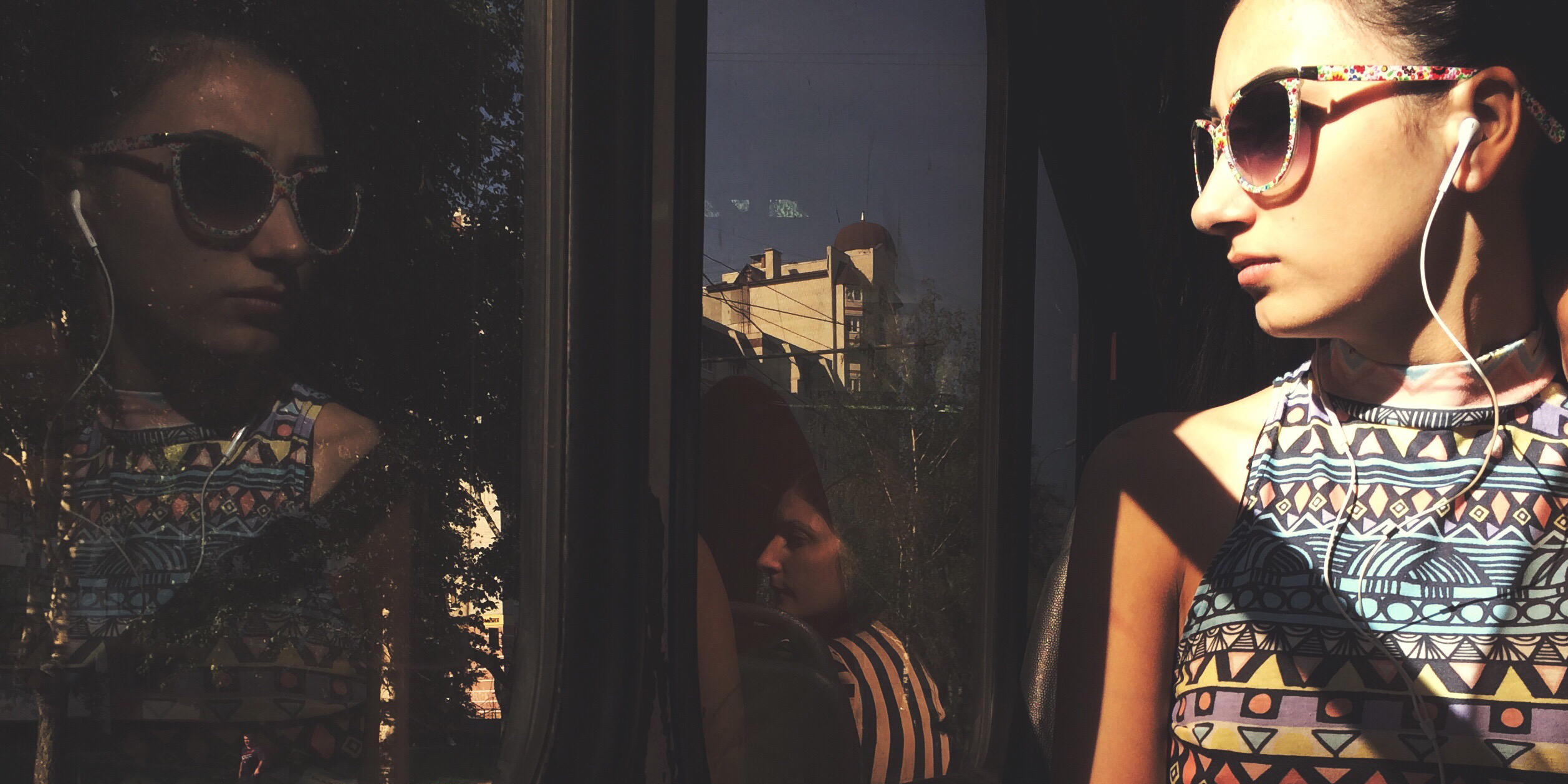 A woman with pale skin and dark hair sits looking out of a window on a train.