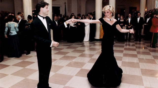 Princess Diana, a white woman with blonde hair, is dancing in a dark blue gown with John Travolta, a white man with brown hair, wearing a tuxedo. Via Getty Images.
