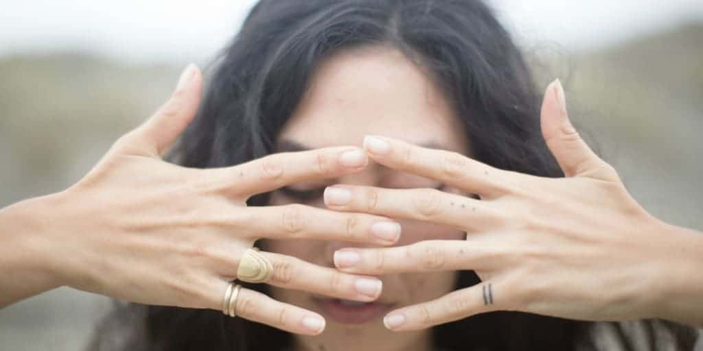 [Image description: A woman locks her fingers in front of her face.] via Unsplash